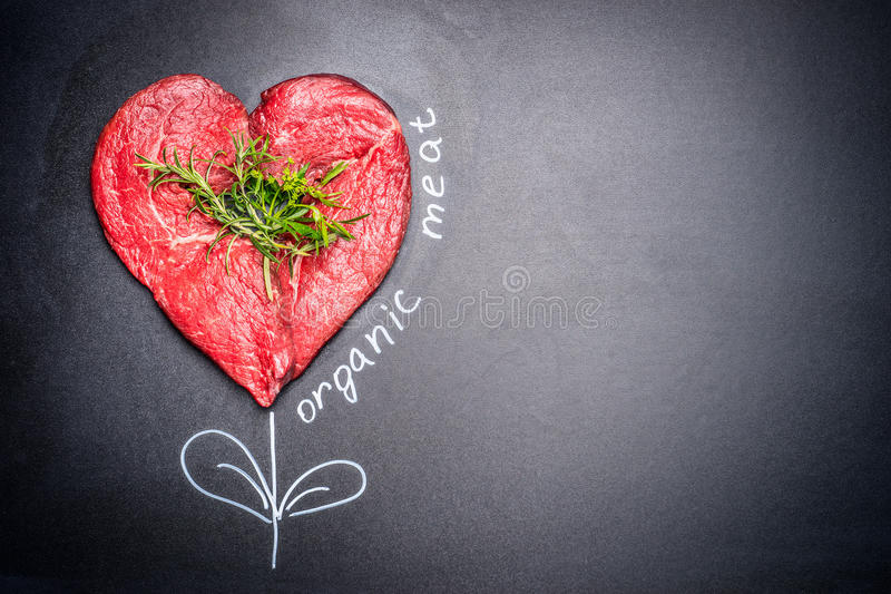 Heart shape raw meat with herbs with painted Organic meat inscription around . Dark chalkboard background. Healthy lifestyle or organic food concept. For Meat royalty free stock photography