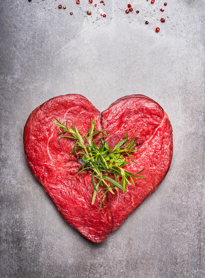 Heart shape raw meat with herbs and text on gray concrete background stock photo