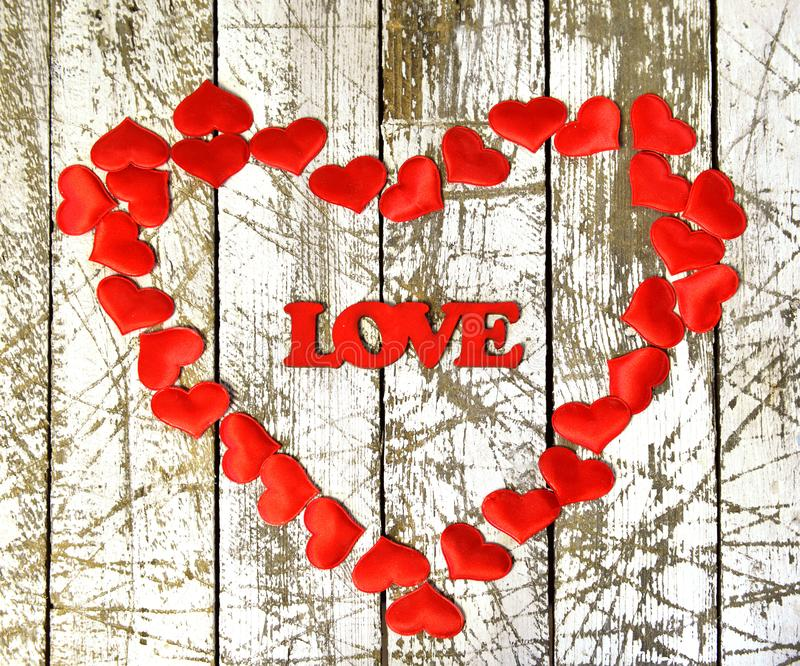 Heart shape from red hearts and the word love on grunge white wooden background royalty free stock photography