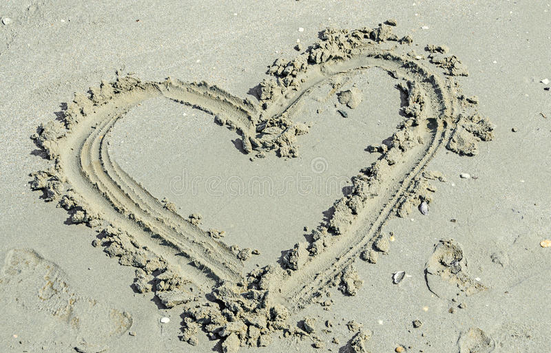 Heart shape sand beach, seaside with water and shells royalty free stock images