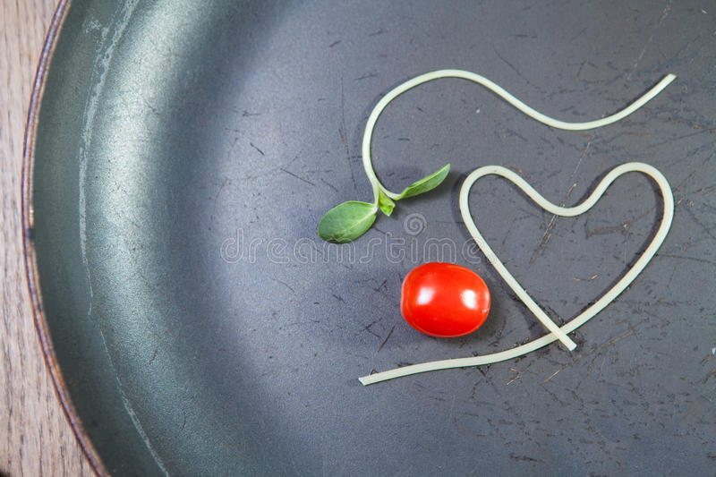 Heart shape of spaghetti and grape tomatoes on Black pan royalty free stock photo