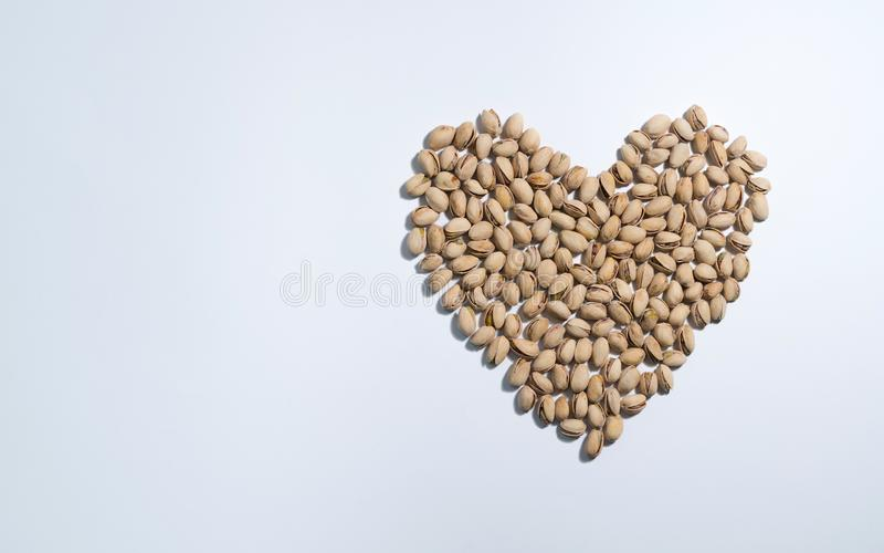 Heart shape stylised of pistachios nuts on white background with space for type. Food mix background, top view, copy space, banner.  royalty free stock photography