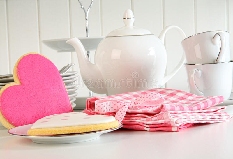 Heart-shape valentine cookies with teapot and cups. On kitchen counter stock image