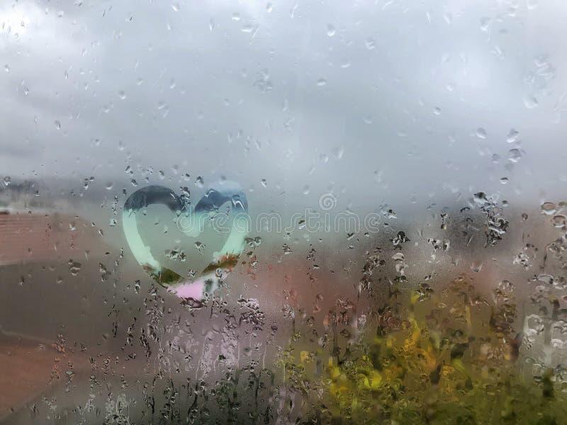 Heart shape on the wet window pane with rain drops royalty free stock photos