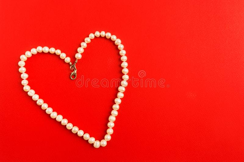 Heart shape of white pearl necklace on red background stock photos