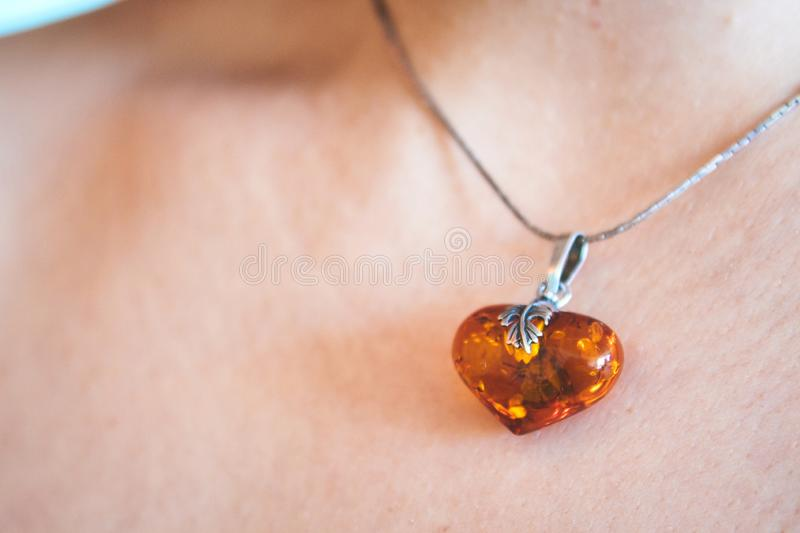 A heart shaped amber pendant worn around the neck of a young woman royalty free stock images