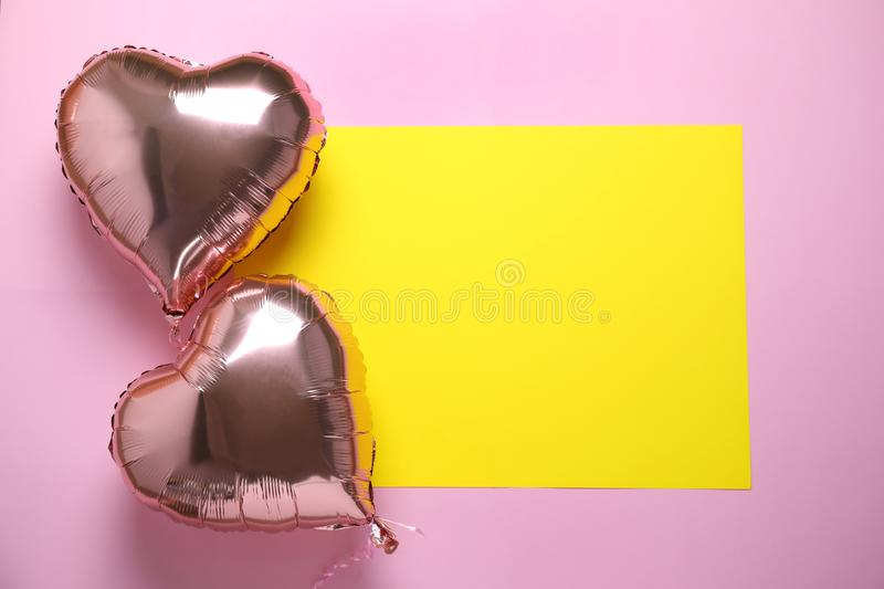 Heart shaped balloons and yellow card on pink background, flat lay. Space for text. Heart shaped balloons and yellow card on pink background stock photos