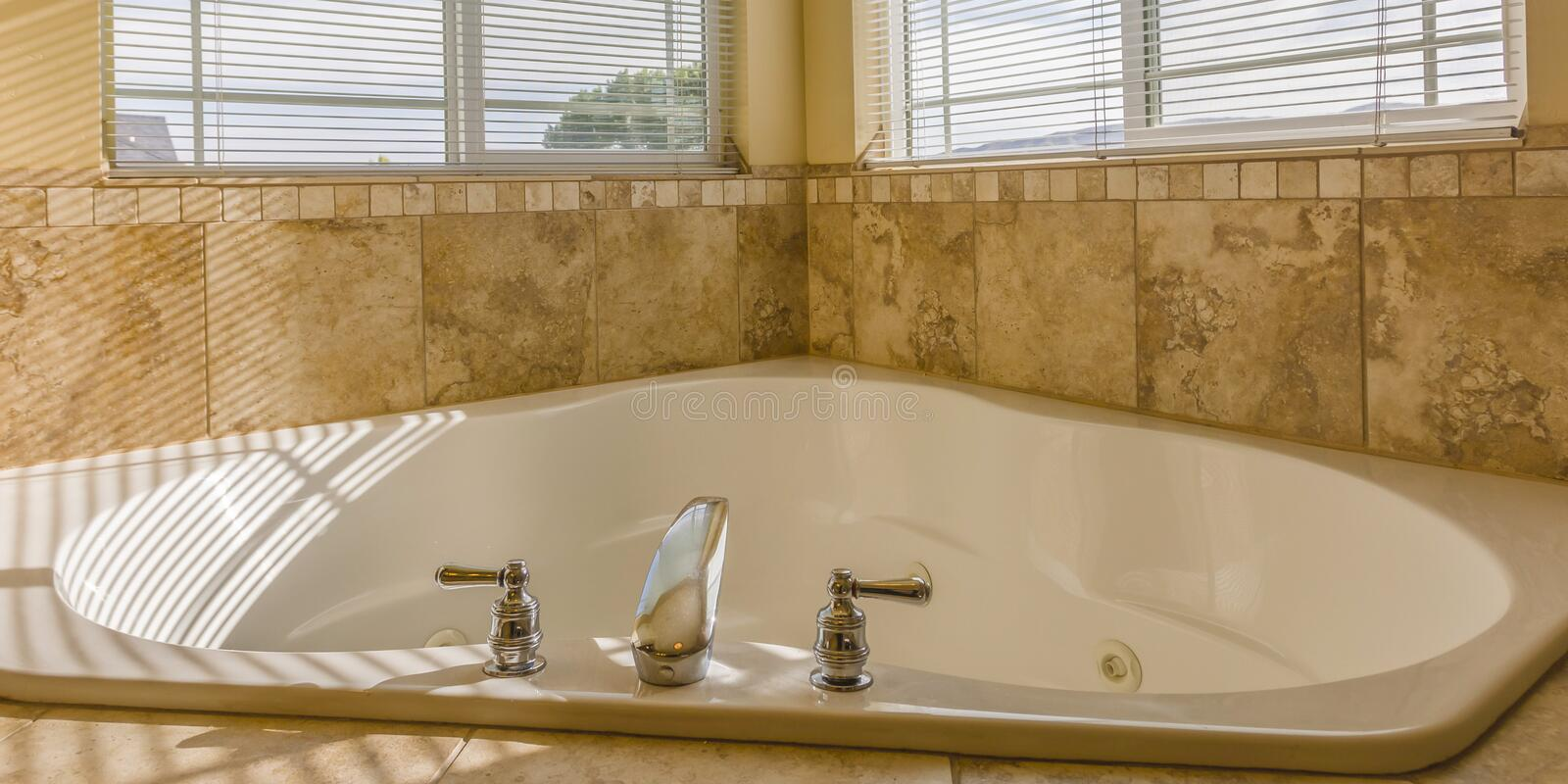 Heart shaped bathtub with jets inside a bathroom. Close up of a bathtub inside a bathroom with sunlight pouring in through the glass windows. The bathtub is royalty free stock photo
