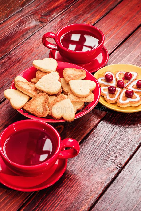 Heart-shaped biscuits with cream and frozen cherries, two cups of tea in bright red cups on a tinted wooden table top. Reflected stock image
