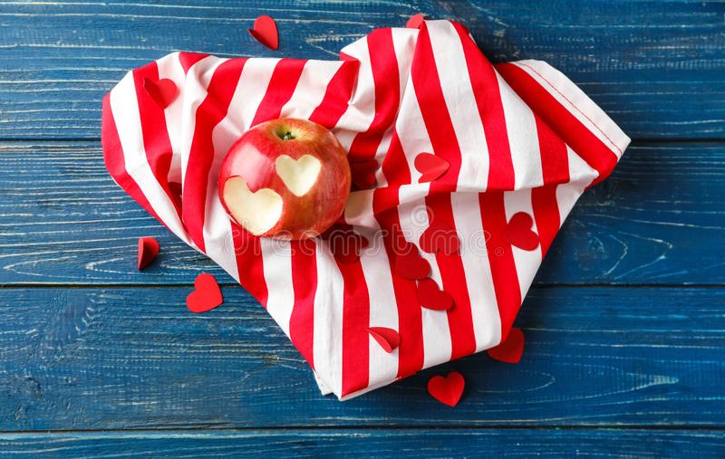 Heart shaped bites on apple with cloth on color wooden table royalty free stock photography