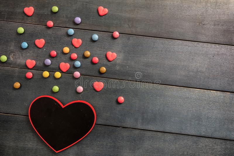 Heart shaped blackboard and candies on wooden background, top view and copy space. stock image