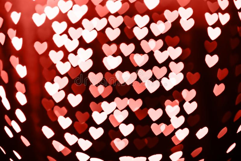 Heart shaped blurred bokeh background with sparkles . Living coral theme - color of the year 2019 royalty free stock photography