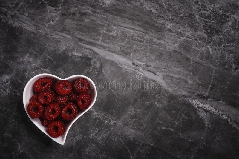 A heart shaped bowl full of fresh organic raspberries on a marble stone background with copy space. A heart shaped white bowl full of fresh organic raspberries stock images