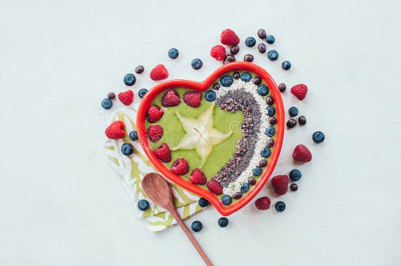 Heart shaped bowl of raspberry, blueberry, cocao nibs, wooden spoon near, isolated over white backgound. Spinach bowl. Fresh fruit stock image