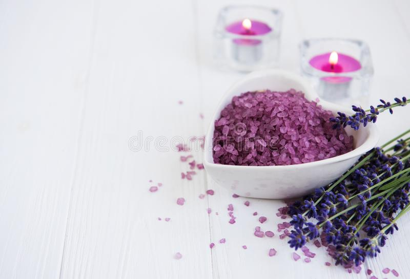 Heart-shaped bowl with sea salt and fresh lavender flowers. On a wooden background royalty free stock image