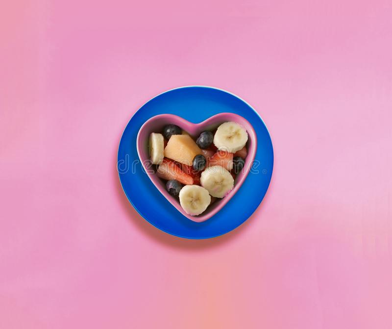 Summer fruits on pink background. Heart shaped bowl with summer fruits stock photography