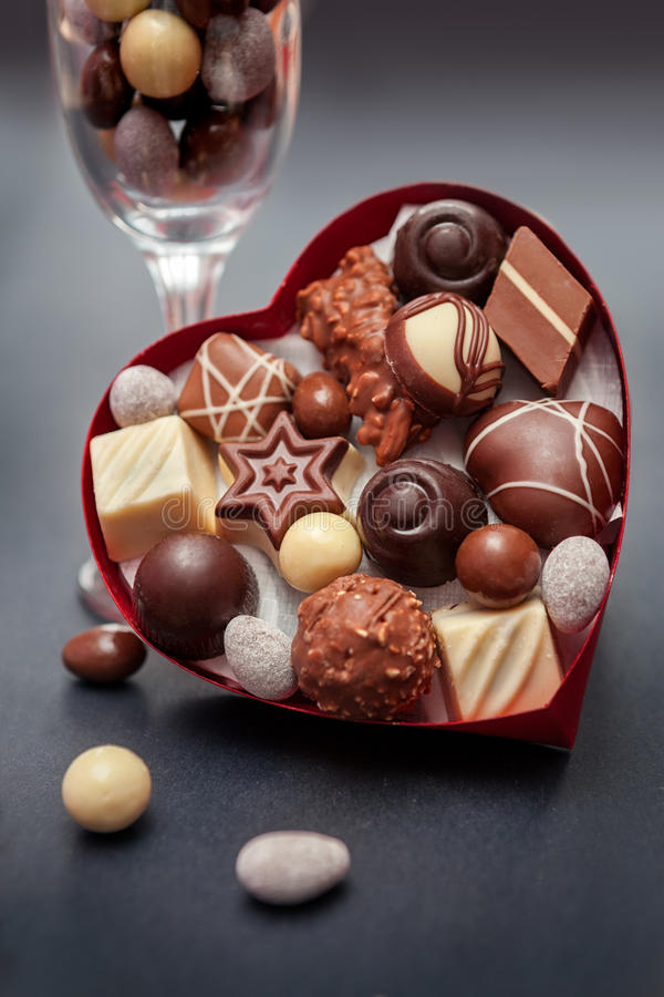 Heart shaped box with pralines on black background royalty free stock photos