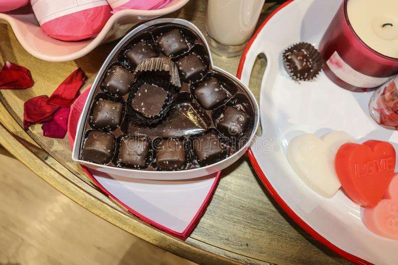 Heart shaped box of sea salted chocolate candy with one eaten surrounded by a candle and rose petals and heart candies - selective. On candy stock photography