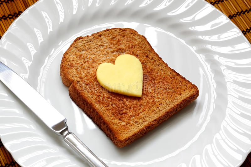 Heart shaped butter on toast stock image