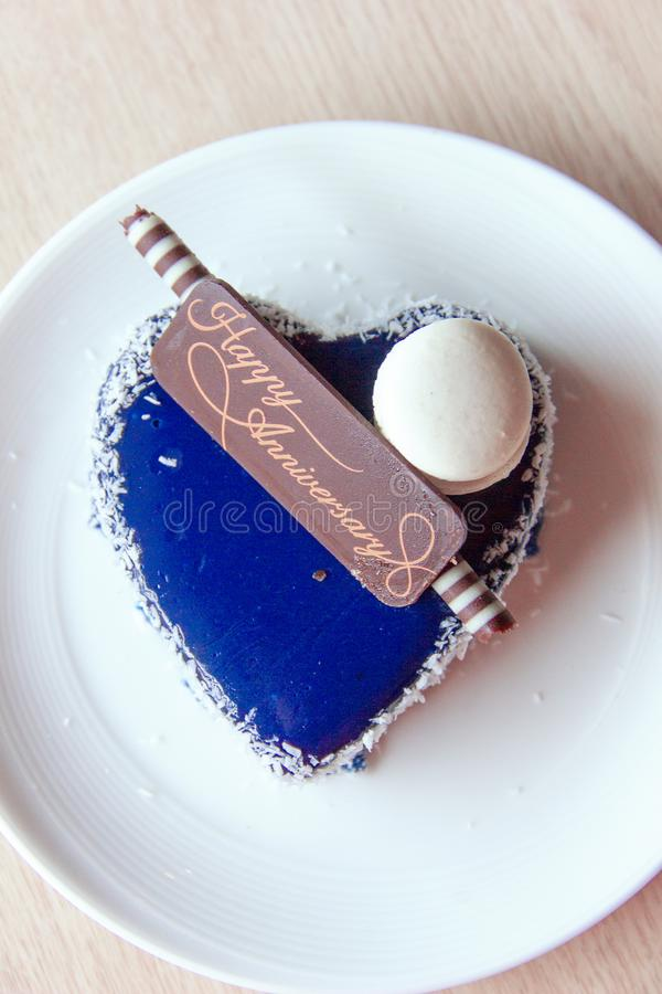 The heart-shaped cake is decorated with blue icing, almond macaroni and coconut topping with a chocolate happy anniversary royalty free stock photos