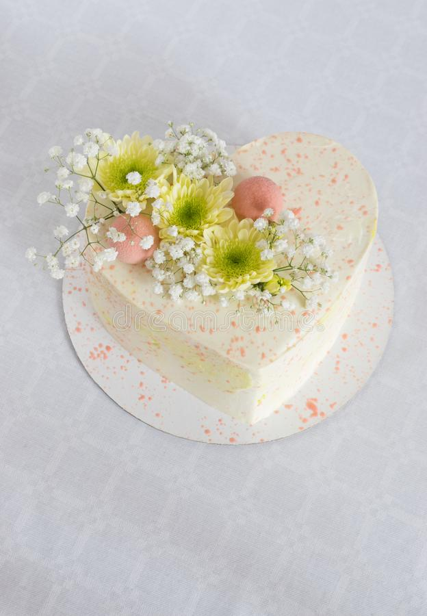 Heart-shaped cake decorated with fresh flowers on a white tablecloth royalty free stock photos