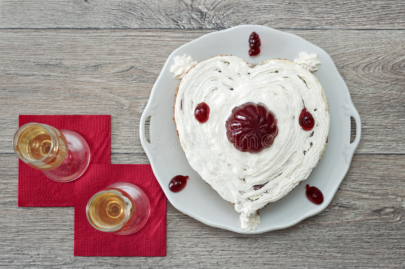 Heart shaped cake with red marmelade and two glasses of champagne served on napkins against wooden background for romantic date royalty free stock image