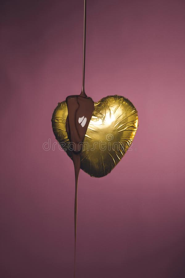 heart shaped candy in golden wrapper with pouring liquid chocolate stock photo
