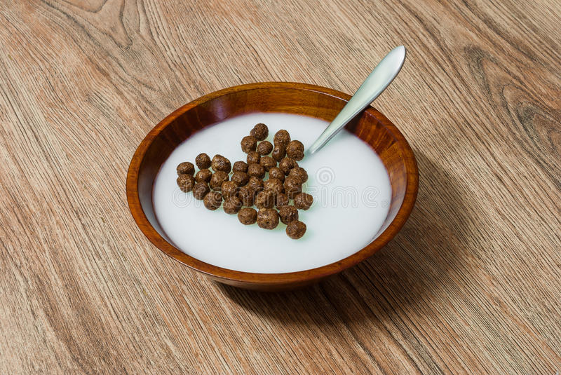 Heart shaped cereal chocolate balls in milk. Heart shaped cereal chocolate balls in wooden bowl with milk royalty free stock photography