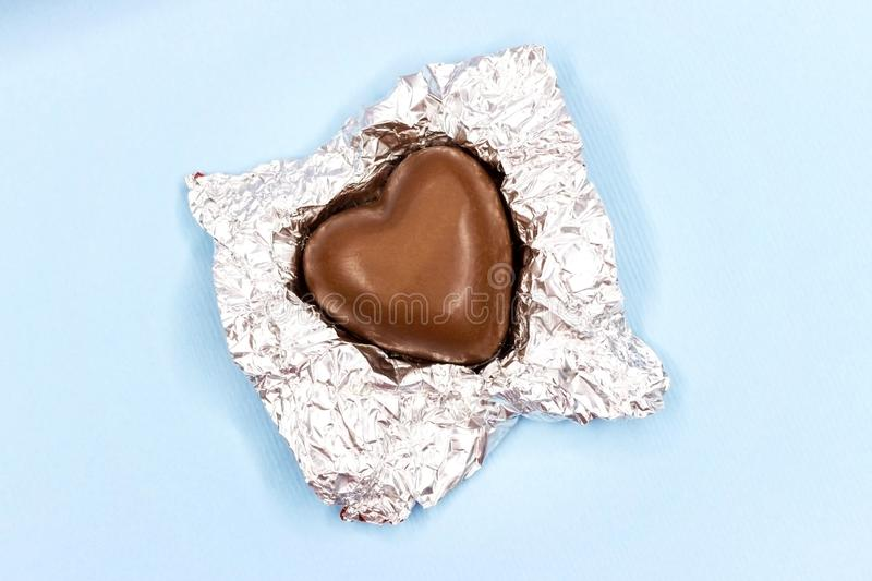 Chocolate hearts in a foil on a blue background stock images