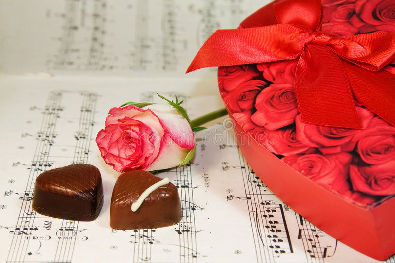 Heart shaped chocolates over classic music notes royalty free stock image