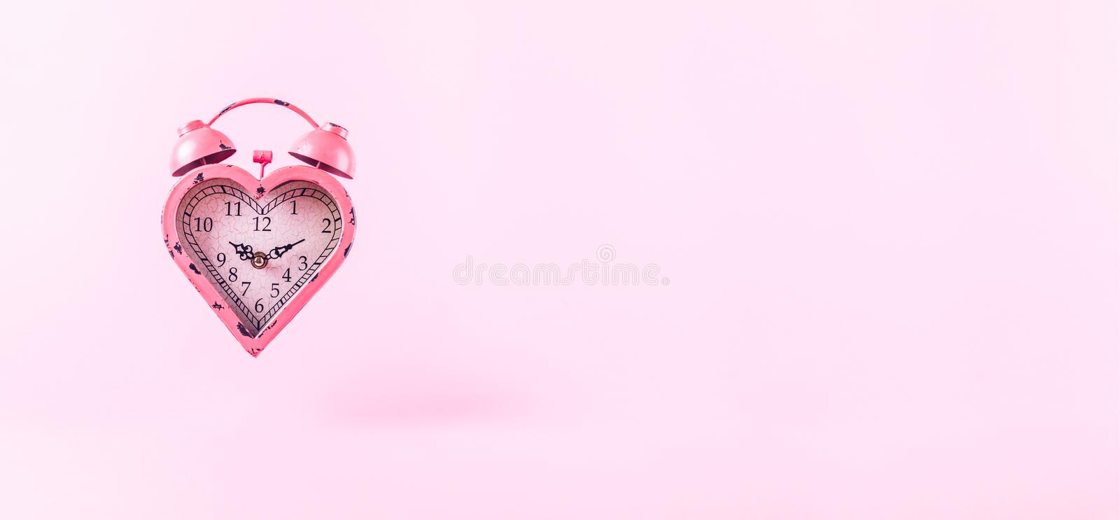 Heart shaped clock on pink background. Valentines day and love royalty free stock photography