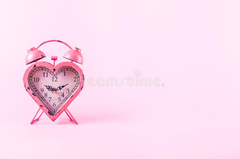 Heart shaped clock on pink background. Valentines day and love royalty free stock images