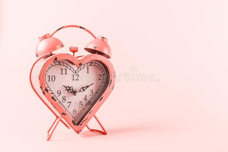 Heart shaped clock on pink background. Valentines day and love infitity and duration concept . Living coral theme - color of the. Heart shaped clock on pink stock photo