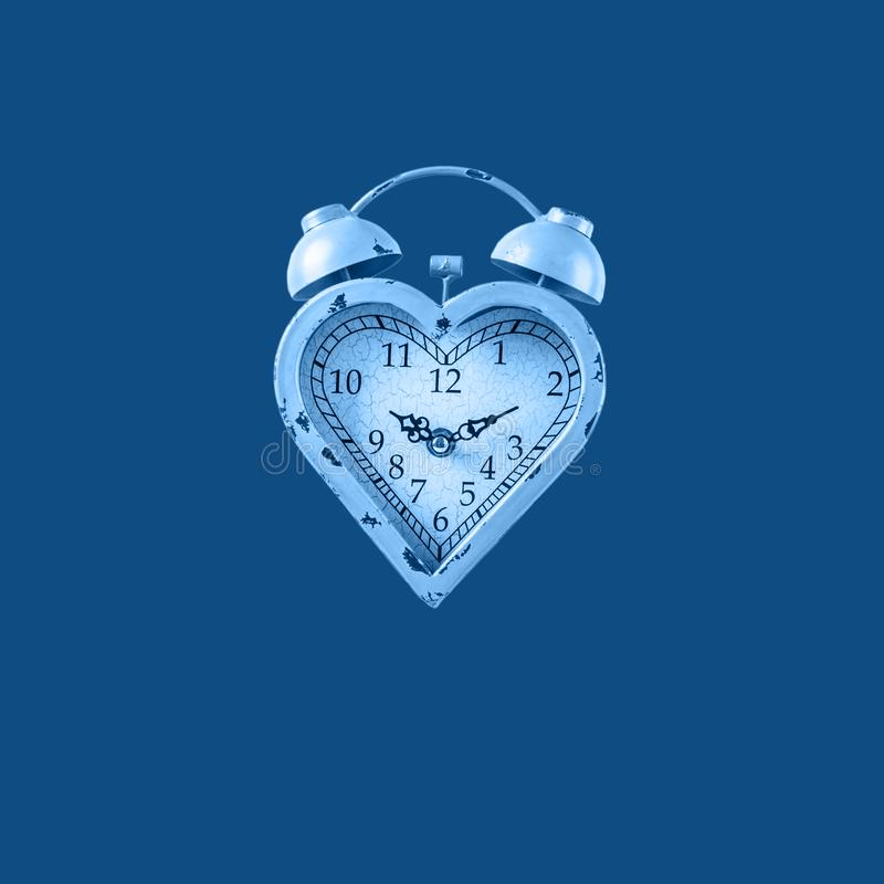 Heart shaped clock on solid background toned in classic blue. Valentines day and love infitity and duration concept. Square stock photography