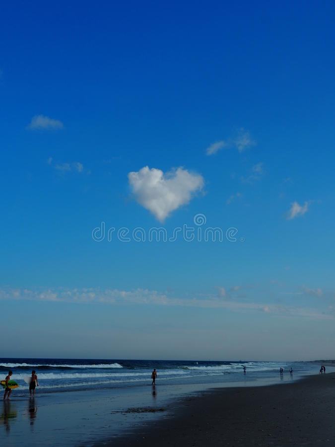 Heart shaped cloud on the beach royalty free stock image