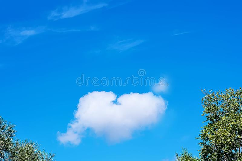 Heart-shaped cloud on a blue sky. Copy space. Concept of love, romance and valentines day.  stock photo