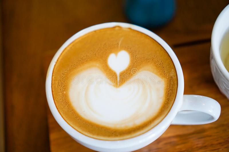 Heart-shaped coffee on a brown wood table.  royalty free stock photos