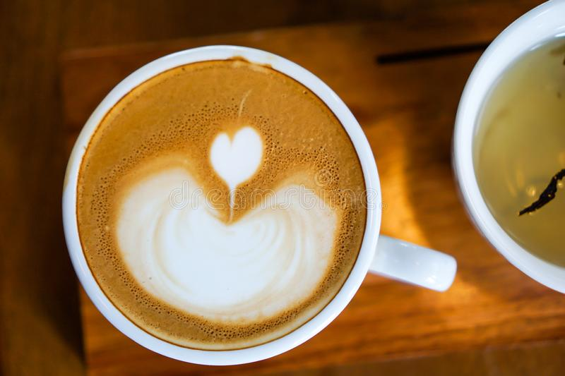 Heart-shaped coffee on a brown wood table.  stock photos