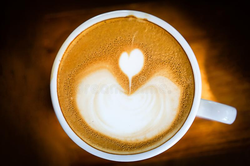 Heart-shaped coffee on a brown wood table.  royalty free stock photo