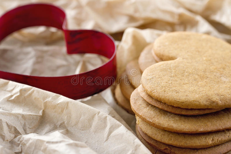 Heart shaped cookie cutter and a pile of brown gingerbread cookies. Red heart shaped cookie cutter and a pile of brown homemade Christmas gingerbread cookies stock photo