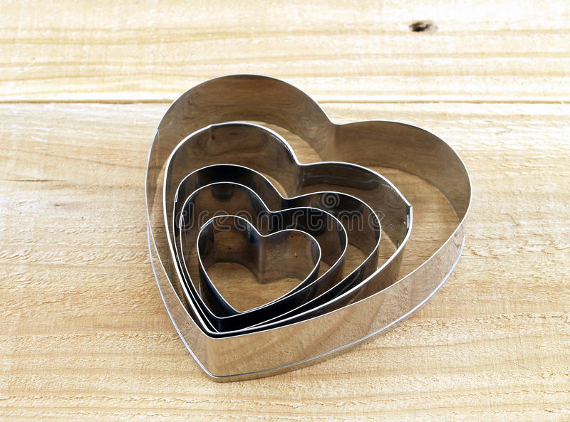 close up many size of silver heart shaped cookies cutter on brown wooden table royalty free stock images