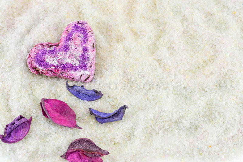 Heart shaped cookie and flower petals royalty free stock photography