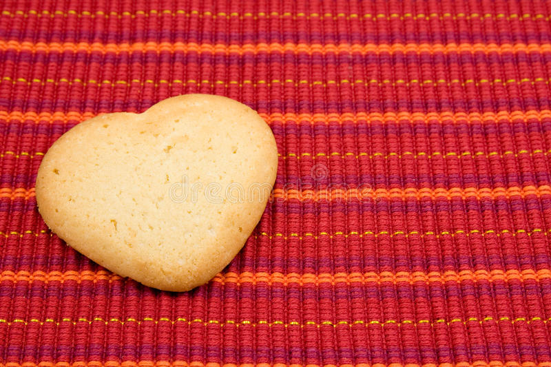 Heart shaped cookie on red tablecloth stock photos