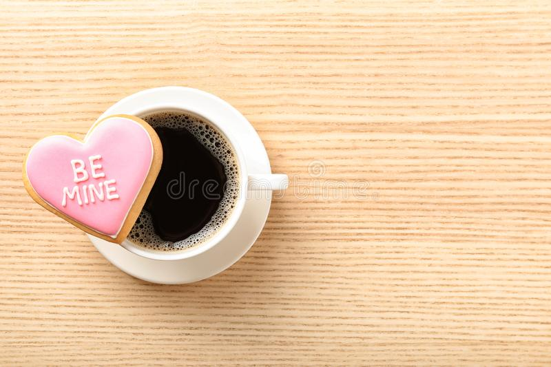 Heart shaped cookie with written phrase Be Mine and cup of coffee on wooden background, top view. Space for text royalty free stock photos