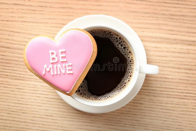 Heart shaped cookie with written phrase Be Mine and cup of coffee on wooden background, top view. Valentine`s day treat stock photos