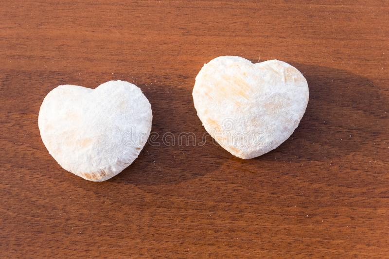 Heart shaped cookies covered with powdered sugar on wooden table. Top view stock photos