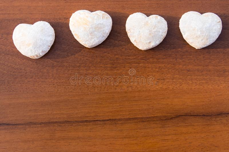 Heart shaped cookies covered with powdered sugar on wooden table. Top view, copy space royalty free stock photos