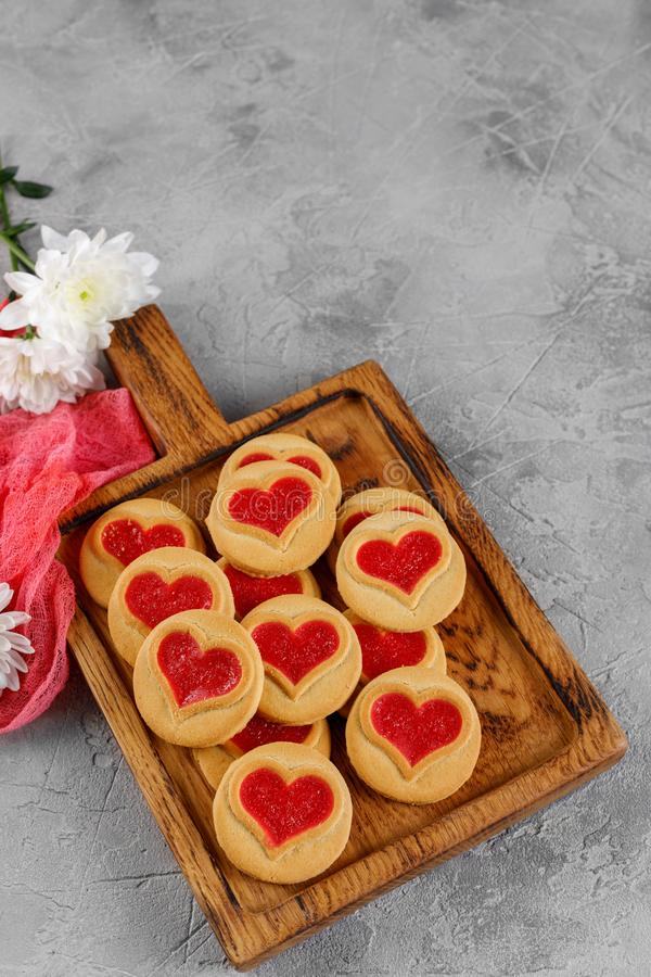 Heart-shaped cookies filled with chrysanthemum flowers on a wooden board. Concept for Valentine`s Day stock photos