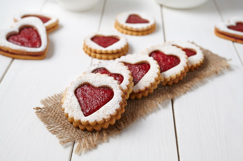 Heart shaped cookies with jam, delicious homemade holiday surprise sweet on white wooden background for Valentines day stock image