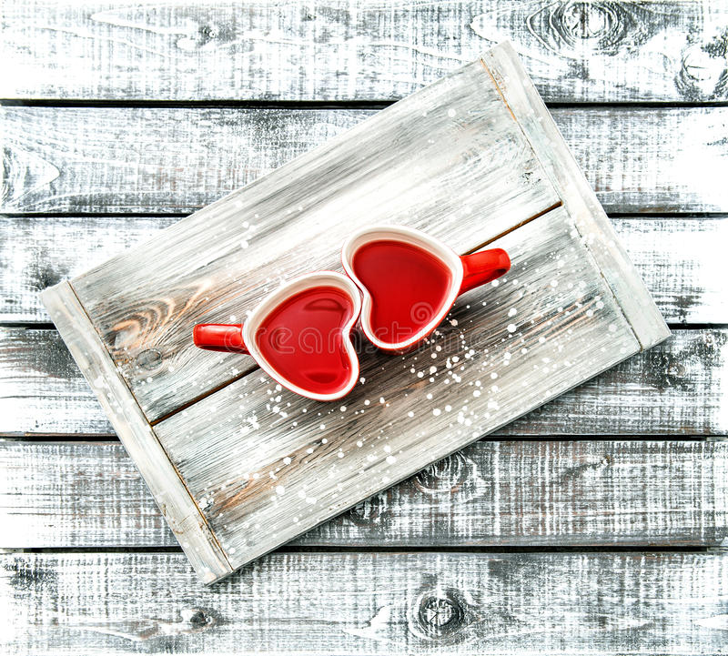 Heart shaped cups red tea drink Valentines day vintage. Heart shaped cups with red tea drink on rustic wooden background. Valentines day concept. Vintage style stock photo